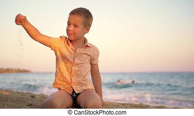 Child playing with sand by the sea at sunset