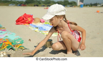 Child playing with sand on beach