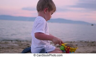 child playing with sand on the beach at sunset time