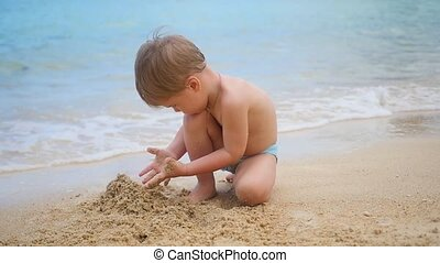 Child playing with sand on the beach on a sunny hot day