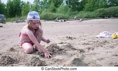 Child playing with sand on the beach. Summer Sunny day, good mood.