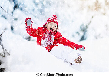 Child playing with snow in winter. Boy in snowy park. - ...