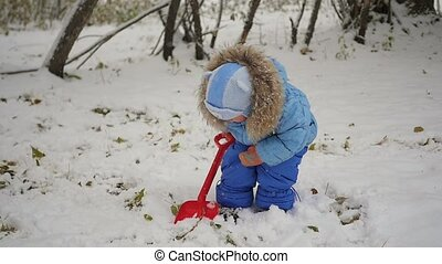 child playing with snow shovel in the park
