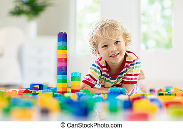 Child playing with toy blocks. Toys for kids.