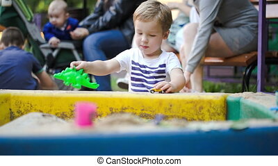 Child playing with toys in sand-pit