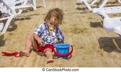 Child Playing With Toys In Sand