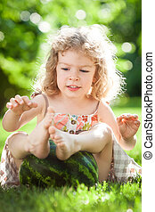 Child playing with watermelon