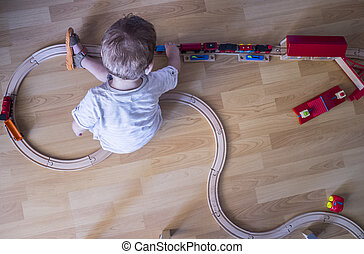 Child playing with wooden toy train