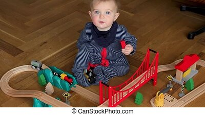 Child playing with wooden train. Baby girl play with train...