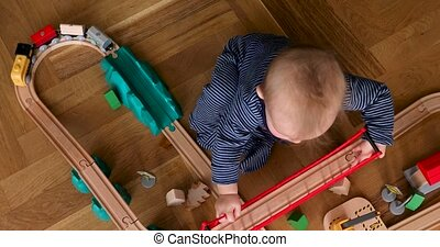 Child playing with wooden train top view - Child playing...