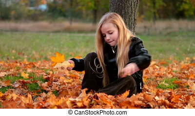 Child playing with yellow fallen leaves sitting under tree in autumn park
