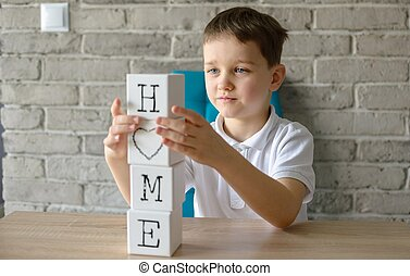 Child playing wooden bricks with letters making word home.