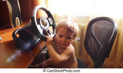 child plays at a computer desk with a steering wheel