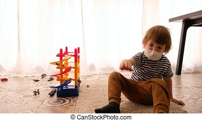 Cute children boy in medical mask is sitting at home in quarantine. Kid play with toy cars. Entertainment for the children during quarantine. Self isolation
