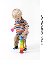Child plays educational toys (pyramid) isolated on white