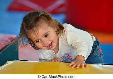Child Plays in Play Center - A girl toddler plays in an...