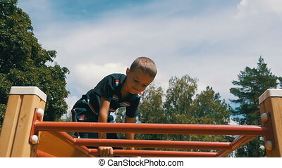 Child Plays in the Playground on the Uneven Bars against the Sky in Slow Motion