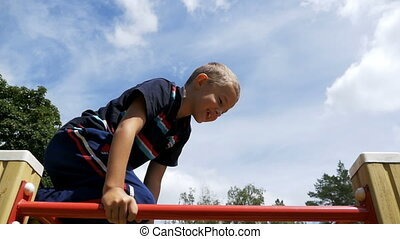 Child Plays in the Playground on the Uneven Bars against the...