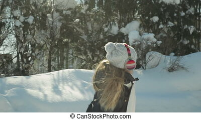 Child plays in the winter Park - little funny girl with...