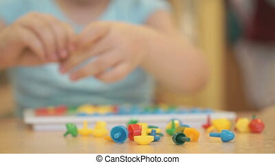 Child plays the intellectual educational game at the table at the kindergarten