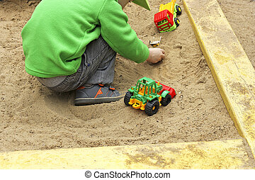 Child plays with toy cars.