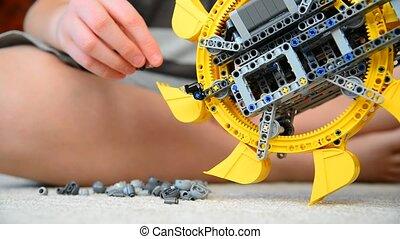 child plays with toy excavator