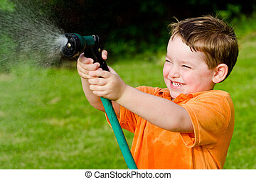 Child plays with water hose outdoors during summer or spring...
