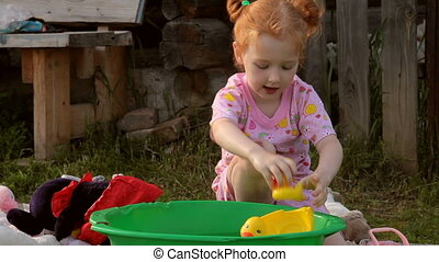 Child Plays With Yellow Rubber Duck in a Basin With Water. In the Backyerd