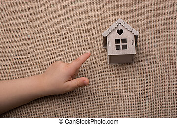 Child pointing  at a model house