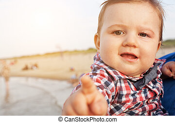 Child pointing at the camera with funny expression on the beach