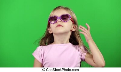 Child posing for video cameras with glasses. Green screen....