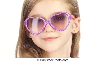 Child posing for video cameras with glasses. White background. Close up