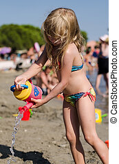 child pouring water on the beach