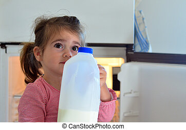 Child Poverty - Hungry poor little girl holds a bottle of...