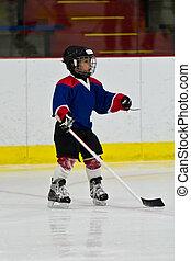 Child practicing ice skating and hockey