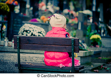 child praying in cemetery