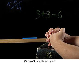 child praying in school - Child's hands folded in prayer on...