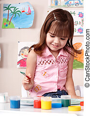 Child preschooler painting in classroom.