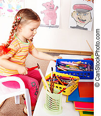 Child prescooler with  pencil in play room.