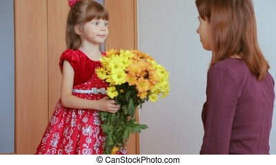 Child presenting flower to her mother slow motion