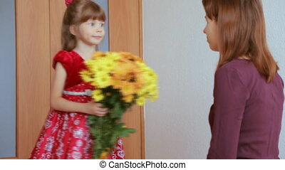 Child presenting flower to her mother