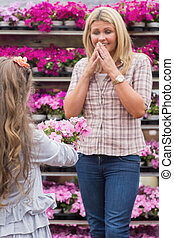 Child presenting flowers to her mother in garden center