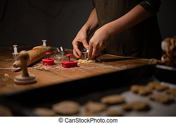 Child pressing cookie cutter in rolled pastry dough