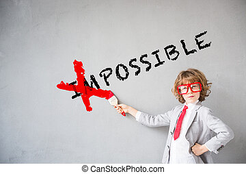 """Child pretend to be businessman. Kid erasing text """"impossible"""". Imagination, idea and success concept. Copy space for your text"""
