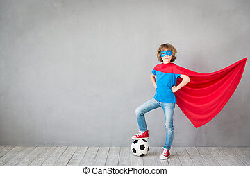 Child pretend to be soccer superhero. Kid playing with ball at home. Success, win and imagination concept
