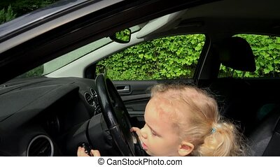 Child pretends driving car sitting on front driver seat with...