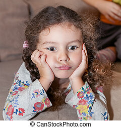 Cute little girl with curly hair, brown eyes lying on the bed propped up hands head