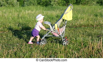 child pushes stroller on summer lawn