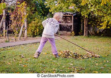child raking fallen leaves