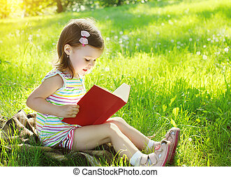 Child reading a book on the grass in sunny summer day